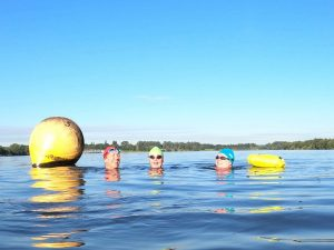 Swimmers in a lake, near to yellow buoys